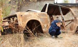 A little girl is crying near the burnt car. War in Donetsk. War Nagorno-Karabakh. Burned-out car.