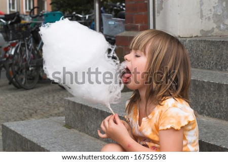 A little girl is eating a cotton candy on a children`s holiday.
