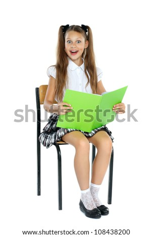 a little girl is in a school form which sits on a chair and reads an interesting book. Isolated on a white background