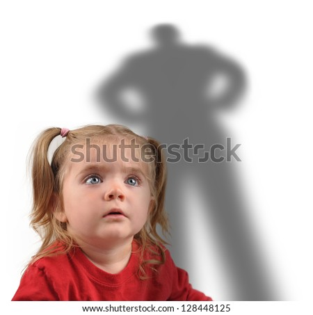A little girl is looking up at a scary shadow of a man on a white background for a fear or kidnapping concept.