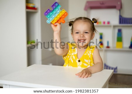 A little girl is playing at a table with a pop it toy. A fascinating sensory toy for development. Colorful popit toy.A simple dimple. The girl is passionate about toys. Laughter and fun.