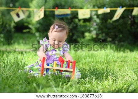 A little girl is playing with colorful wooden toys on the grass, in the background hanging kids drawings