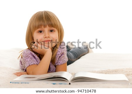 A little girl is reading a book on the carpet; isolated on the white background