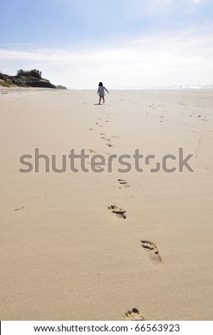 A little girl is running away on a wide, empty beach, leaving footprints.