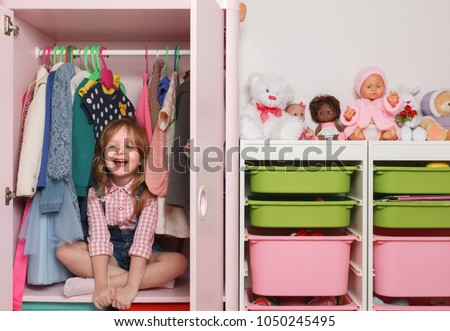 A little girl is sitting in a closet with a children's department. Storage system for children's things and toys