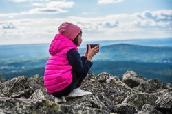 A little girl is sitting on top of a mountain, looking into the distance and drinking tea from a large mug. Russia, Ural