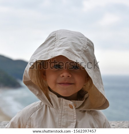 A little girl is wearing a raincoat jacket with hood against a stormy sky. Magnetic and intense look. Childhood concepts. Environmental concepts. Climate concepts.