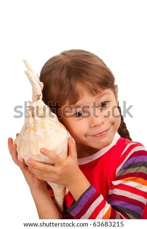 a little girl listening to the sea by a seashell