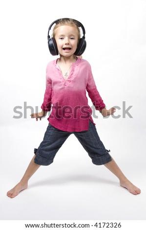 A little girl listens to music through a pair of wireless headphones