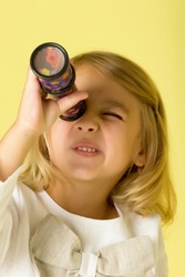 A little girl looks into a telescope or in a kaleidoscope.