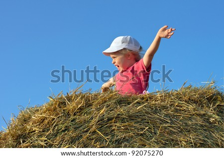 A little girl meets a sunset sitting on the hay
