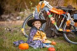 A little girl on a Halloween holiday in nature, a child sits near a bicycle decorated with garlands with ghosts and pumpkins.