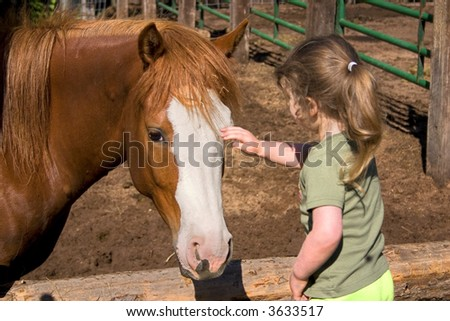 a little girl petting a beautiful horse