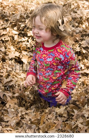 a little girl playing in a pile of leaves