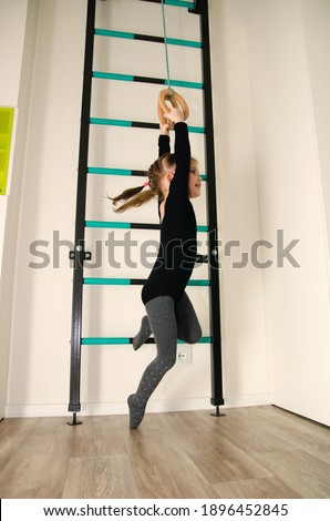 A little girl plays on the stairs with gymnastic rings in active games at home. Foto stock ©