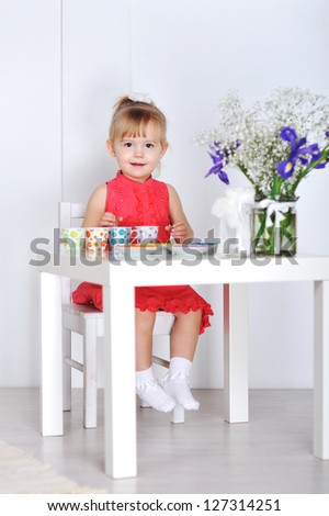 A little girl plays with dolls and dishes