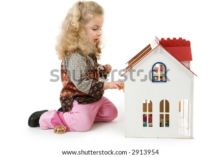 a little girl plays with her doll´s house