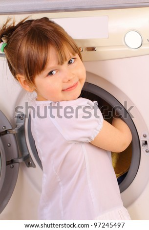 A little girl puts the towels into the washing machine