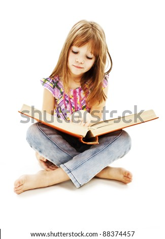 A little girl reading a book on the floor. Isolated on white background