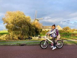 A little girl rides a bicycle on the bike path near the mill. A typical Dutch child goes to school or to a sports lesson. Happy Dutch kid.