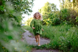 a little girl runs along the path happy in the Park in the spring