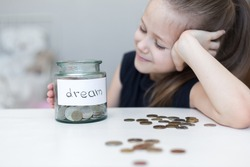 A little girl saves money for a dream. child counts and puts coins in a glass bottle in her room. The child saves money on the concept of the future