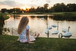 A little girl sits by the lake on the green grass at sunset on a summer day and looks at the olive sky, water and white swans swimming. Summer landscape with a child, beautiful white birds, trees