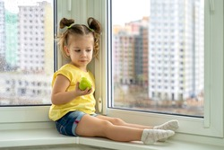 a little girl sits by the window, sad and holds an apple in her hands. quarantined children