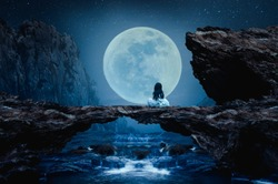 A little girl sits on a stone bridge on a beautiful full moon night.