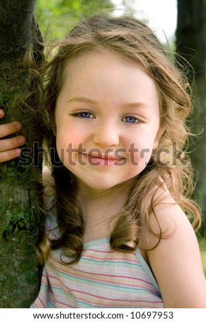 a little girl sitting in a tree - stock photo