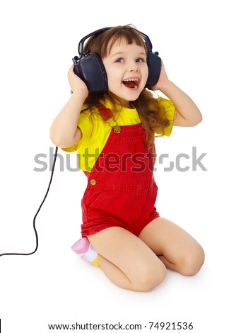 A little girl sitting on a white background with large earpieces