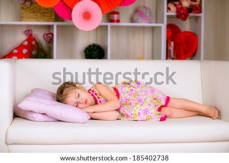 A little girl sleeping on a pink pillow