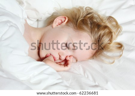 a little girl sleeping, thumb-sucking and having sweet dreams