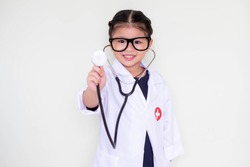 A little girl smiling, dressed in a Doctor. Doctor headphones handle up poses check.