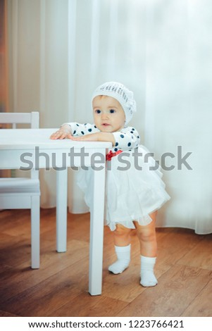 A little girl standing near a white table in a dress with black polka dots Stock fotó ©