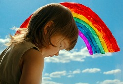a little girl stands at the window with a rainbow painted in gouache on the glass against a blue sky with white clouds. symbol of happiness and love. children and rainbows