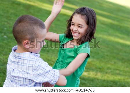 A little girl swings her arms at her brother as they rough house playfully.  Slight motion blur on the arms.