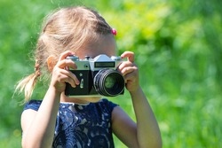 A little girl takes a picture with a retro film camera in the summer in the park. Little pretty child baby girl in light dress holding retro vintage photo camera on green grass in city park.