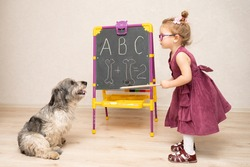 a little girl teacher in a dress and glasses teaches a dog to read and count. She writes letters and numbers on the blackboard. The little girl scolds her dog for being a bad student.