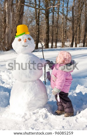 A little girl touching a snowman