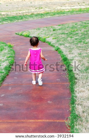 A little girl walking down a sidewalk dressed in a pretty pink dress and sandals.