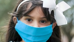 A little girl wearing a mask as a new normal during the COVID19 pandemic stares somberly into the camera.