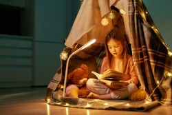 A little girl wearing pyjamas sitting on a floor cross-legged barefoot in a self-made hut made of a plaid, reading a book aloud with her teddybear and fancy garlands all around her spacy room at home