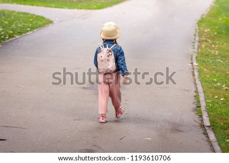 6b88b366a9 A little girl with a backpack going along the sidewalk. View from the back. Stylish  little girl with a backpack