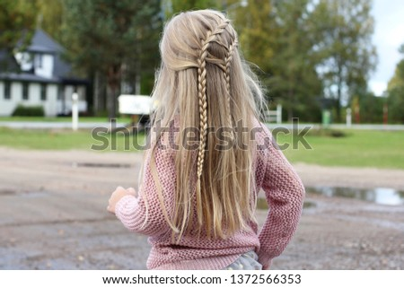 A little girl with a braided hairstyle. Two waterfall braids on a child.