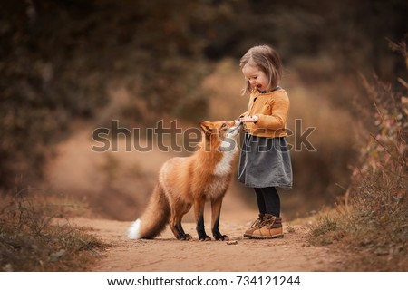 a little girl with a Fox in autumn forest