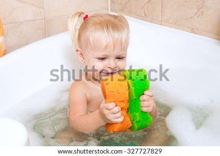 a little girl with blond pigtails bathes in a bath with foam. little girl playing with colorful washcloths in the bathroom. Cheerful little girl bathing. Multicolored sponges in the bathroom with foam