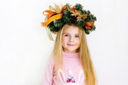 a little girl with blonde hair in a wreath with Christmas tree branches looks into the frame and smiles sweetly with dimples on her cheeks close up on a white background