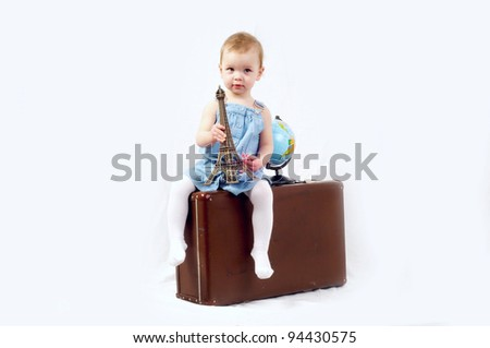 A little girl with globe and old baggage