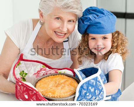 A little girl with her grandmother looking at the camera at home